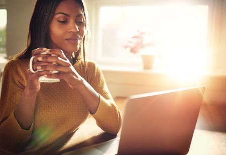 trabajo social: mujer adulta sonriente sentado cerca de la ventana brillante, mientras que mira el ordenador portátil abierto sobre la mesa y sostiene la taza blanca