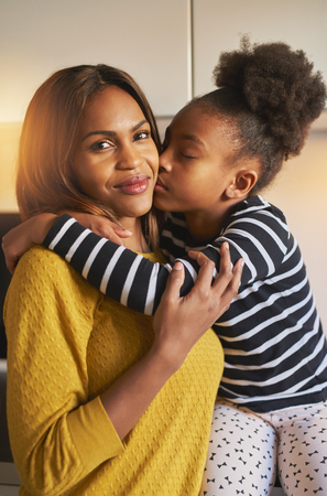 hugs and kisses: Portrait of beautiful black family mom and daughter, kissing and love