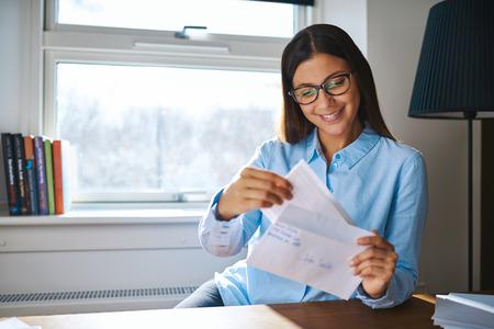 젊은 비즈니스 기업가 그녀의 메일 집에서 그녀의 손에 열려있는 편지와 함께 앉아 그녀의 메일을 검사