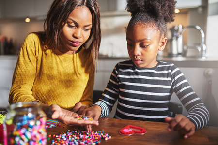 african mother: Serious little girl in striped shirt choosing beads from hand of woman sitting with her at table indoors