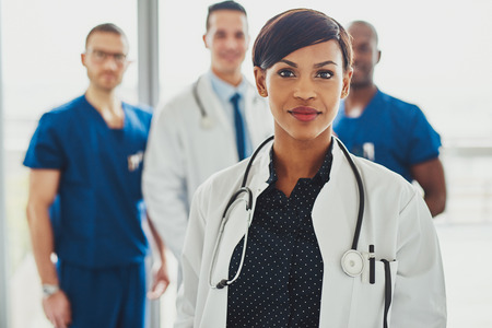 Confident female doctor in front of team, looking at camera smiling, multiracial team with black female doctor Stockfoto