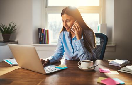 Femme travaillant sur un ordinateur portable au bureau tout en parlant au téléphone, rétro-éclairé lumière chaude