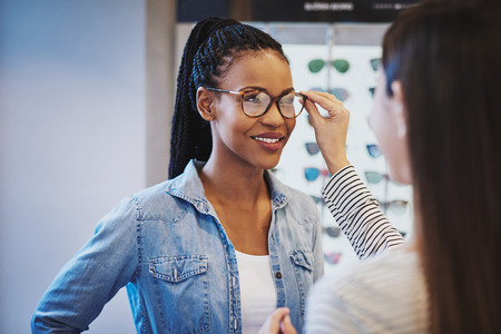 selects: Optometrist fitting glasses on an attractive African American woman customer inside a store as she selects a frame Stock Photo