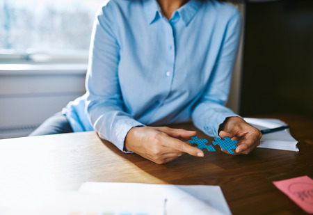 people problems: Cropped view close up of woman at desk assembling two jigsaw puzzle pieces for concept about self employed people solving problems Stock Photo