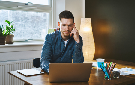 work at home: Worried entrepreneur young man working at desk on laptop looking serious Stock Photo