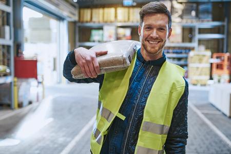 Lachende jonge man werken in een magazijn staan met een zak van het product over zijn schouder kijken verbaasd naar de camera, close-up bekijken Stockfoto