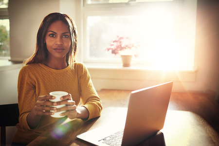 weekend break: Serious young single female sitting at table holding coffee cup next to open laptop with bright sun coming through window