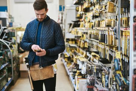 Jonge klusjesman controleert informatie op zijn mobiele telefoon alvorens een aankoop in een hardwarewinkel te doen