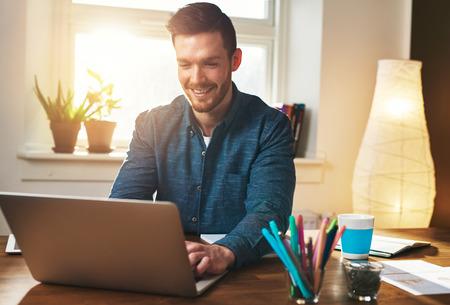 성공적인 기업가 만족에서 웃고 그는 홈 오피스에서 일하고있는 동안 자신의 노트북 컴퓨터에 정보를 확인, 뒤에 태양 플레어