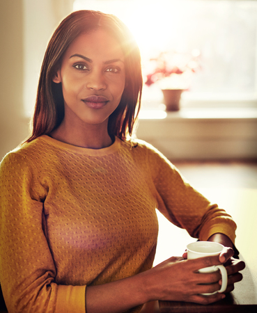 introspective: Close up of calm beautiful black single female in yellow sweater holding white mug next to bright sunlight in window Stock Photo