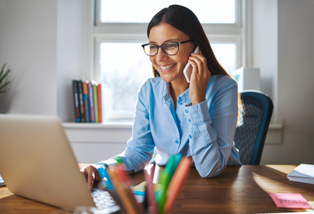 笑顔と電話で眼鏡、背景の明るい窓とデスクでノート パソコンでの作業で 1 つの幸せな女性のビジネス所有者