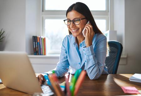 el dueño individual femenina feliz de negocios con sonrisa y lentes en el teléfono y que trabaja en el ordenador portátil en el escritorio con ventana brillante en el fondo