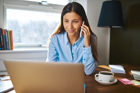 e business: Cheerful young female adult business owner with grin on phone while working on laptop computer at desk next to coffee cup with window and lamp in background