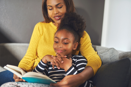teaching children: Black mom and daughter reading a book sitting on sofa smiling