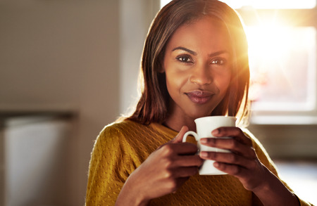 Smiling friendly young black woman drinking a cup of fresh coffee as she relaxes at home backlit by a bright high key sun flare