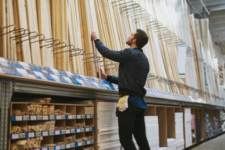 carpintero: Carpintero selección de longitudes de madera cortada de un estante en una ferretería, de bajo ángulo de visión trasera desde el lado