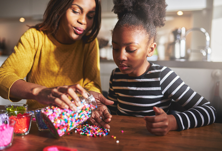 colorful beads: Helpful African mother taking out colorful beads from container in hand on wooden table for child sitting in kitchen