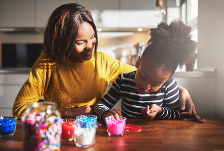 pretty smile: Happy woman in yellow sweater watching child working with beads with arm over her shoulder while seated at kitchen table indoors Stock Photo