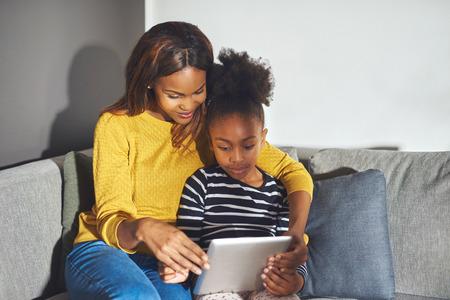 mama e hija: Madre e hija con la tablilla que se sienta en el sofá concentrado en el aprendizaje