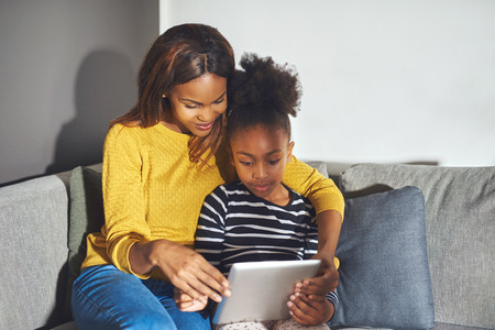 african american mother and daughter: Mom and daughter with tablet sitting in sofa concentrated on learning