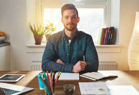 authoritative: Confident authoritative young businessman working from a home office sitting looking at the camera with a thoughtful proud expression