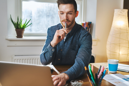 relaxed business man: Relaxed business man working on laptop holding a pen in his mouth looking concentrated