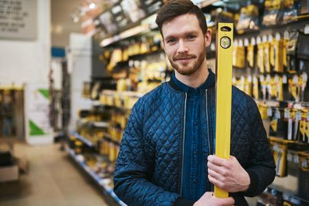 Giovane uomo con una costruttori o carpentieri livello egli sceglie il suo acquisto in un negozio di ferramenta, parte superiore del corpo da vicino