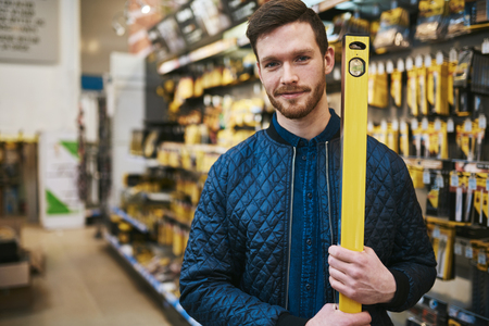 selects: Young man carrying a builders or carpenters level as he selects his purchase in a hardware store, upper body close up