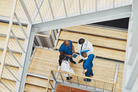 stairwell: Medical team having an emergency discussion standing grouped in a stairwell at the hospital looking up information on a tablet,, view from above down the stairwell Stock Photo