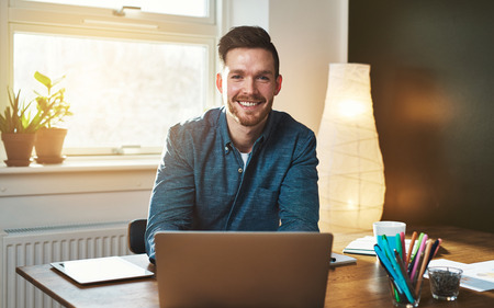 Entrepreneur at office with laptop looking at camera smiling