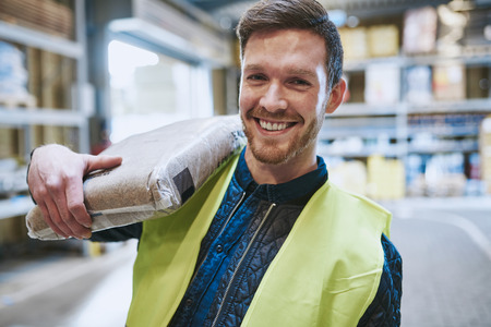 Friendly happy warehouse worker in a high visibility jacket standing in the warehouse with a product bag over his shoulder smiling at the camera, head and shoulders view