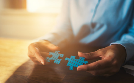 consultant: Business woman connecting puzzles, closeup of hands, success concept