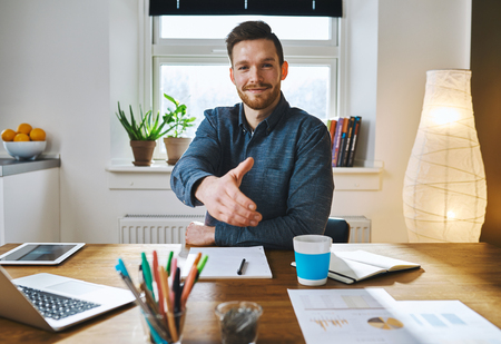 deal in: Smiling businessman leaning across his desk offering his hand in greeting, to close a deal, in partnership or congratulations Stock Photo