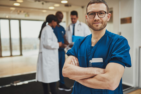 group meeting: Confident relaxed surgeon doctor at hospital with team of doctors in background