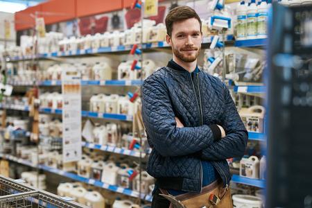 hardware: manitas confía en una ferretería que se coloca entre los bastidores de los productos con los brazos plegables que sonríe en la cámara