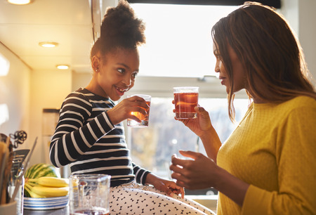 summer house: Mom and child in kitchen drinking lemonade, happy smiling family Stock Photo