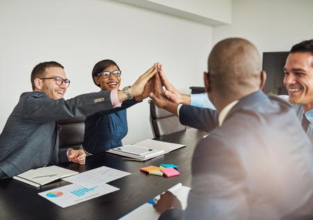 Juichende multiraciale business team schreeuwen en lachen als ze elkaar met een high fives handgebaar feliciteren