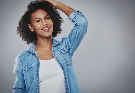 コピー スペース グレーに素敵な暖かいフレンドリーな笑顔でカメラを見て彼女の頭に彼女の手で立っている巻き毛を持つ幸せな快活な若いアフリカ