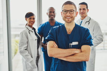 Confident doctor in front of group smiling at the camera, wearing surgeon clothes