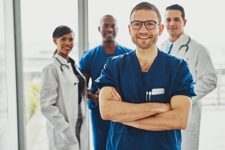 Medico fiducioso davanti al gruppo sorridendo alla telecamera, indossando abiti chirurgici