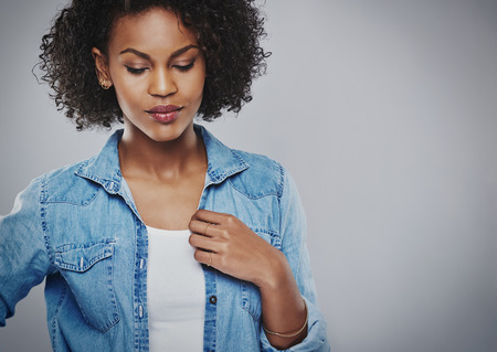 downhearted: Thoughtful attractive young African American woman wearing a casual denim jacket standing with downcast eyes looking down at the floor, over grey with copy space Stock Photo