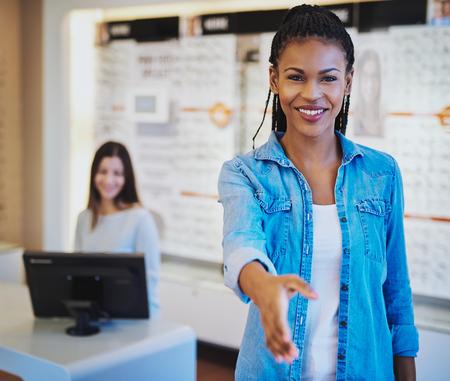 personas saludandose: saludar a un cliente en la puerta con una gran sonrisa y la mano extendida o ofrecen a dar la mano a un acuerdo bastante joven africano americano optometrista