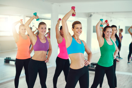 synchronously: Close-up of group of young women doing exercise with dumbbells on triceps synchronously