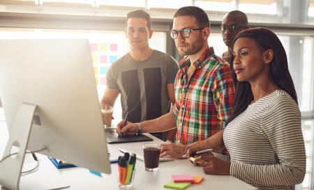 cooperación: Grupo de cuatro empresarios de adultos negros, hispanos y caucásicos vistiendo ropa casual mientras que se coloca alrededor del ordenador para la demostración o presentación