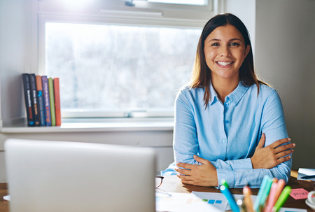 e business: Single confident smiling woman in blue shirt with folded arms at desk behind laptop computer and papers in home office