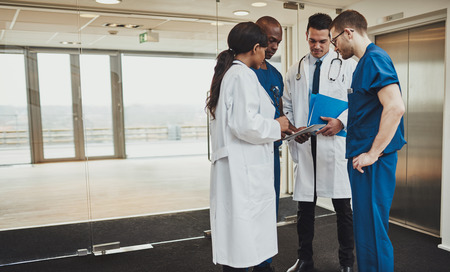 female clothing: Diverse multiracial medical team consulting on a patient records standing in a foyer at a hospital grouped around a tablet computer Stock Photo