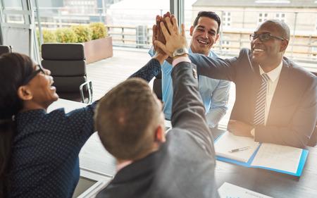 混血の若いビジネス専門家喜びと高い fives を与えている互いを祝福の大喜びのチームがジェスチャーします。