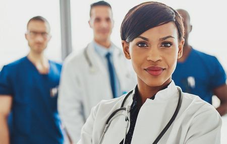 Vrouwelijke dokter voor team, stethoscoop rond nek kijkt zelfvertrouwen