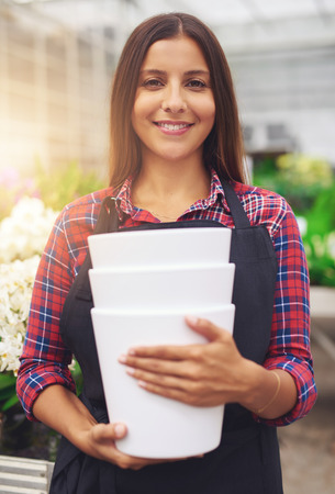 floriculture: Pretty young worker in a floriculture business standing working in the greenhouse holding stacked plastic flower pots as she smiles at the camera