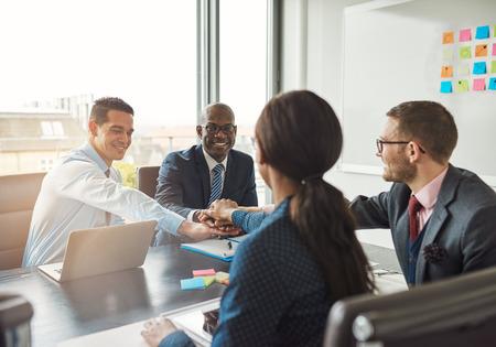 Framgångsrik multiracial affärsgrupp som arbetar tillsammans bekräftar sitt engagemang genom att knyta händerna över ett kontorsbord under ett möte